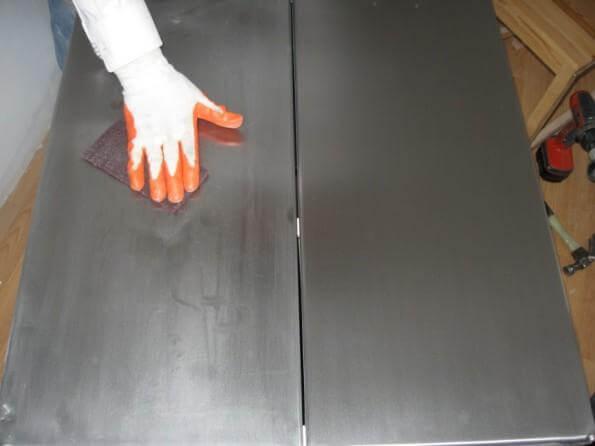 Sanding a metal door.